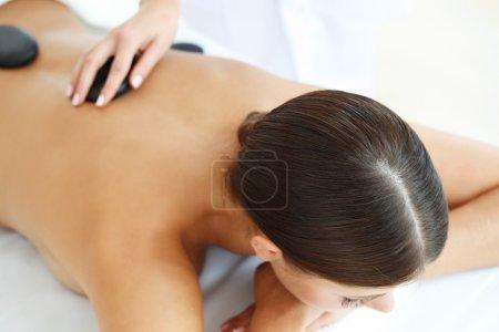 Photo pour Belle jeune femme en spa pour massage aux pierres chaudes - image libre de droit