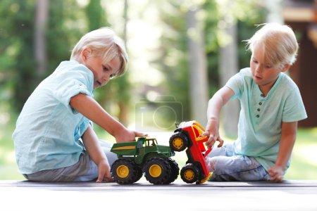 Photo pour Deux frères jouant à l'extérieur avec des voitures jouets - image libre de droit
