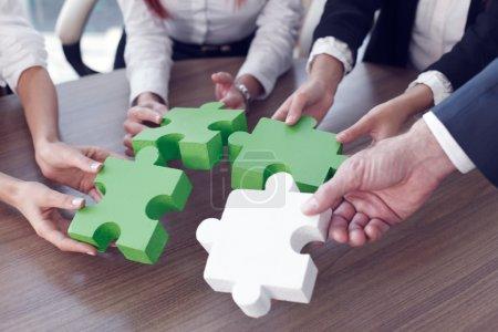 Foto de Grupo de personas de negocios que ensamblan rompecabezas y representan el apoyo del equipo y el concepto de ayuda en la oficina - Imagen libre de derechos