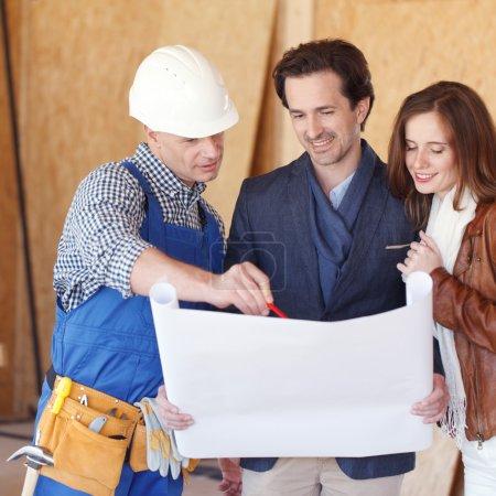 Photo pour Construction : Jeune couple Regardez les plans de la maison avec Builder - image libre de droit
