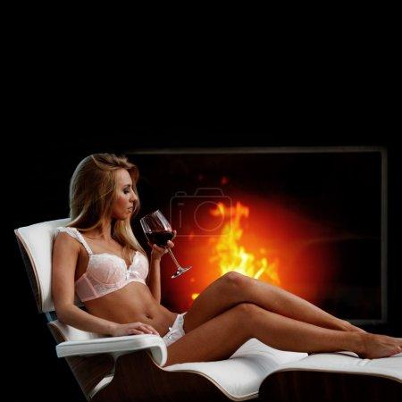 Photo pour Femme sexy en lingerie avec vin près de cheminée - image libre de droit