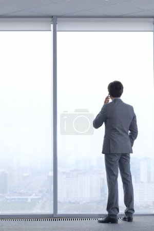 Photo for Businessman standing near window, looking at city and talking by phone - Royalty Free Image