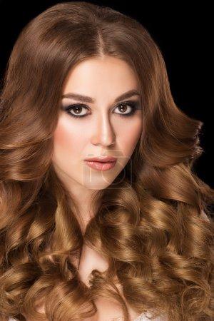 Foto de Retrato de la belleza. Hermosa mujer con el pelo rubio largo oscuro sobre fondo negro. Hermoso maquillaje y estilo de pelo rizado. - Imagen libre de derechos