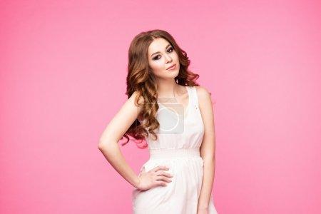 Photo pour Belle fille isolée sur fond rose. Debout, regardant la caméra. Robe blanche et chaussures blanches. belle coiffure et maquillage . - image libre de droit