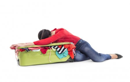 The woman lies on a suitcase with clothes.
