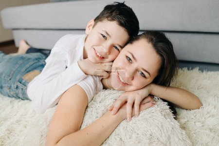 Brother and sister laughing together at home