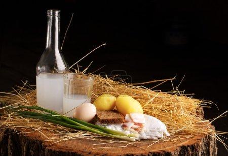 Photo pour Sur une souche dans le foin est bouteille moonshine, pain au saindoux, pommes de terre et oeuf - image libre de droit