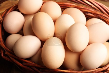 Photo for Eggs in the wooden basket neatly folded and ready for the Easter holiday. Chicken eggs - Royalty Free Image