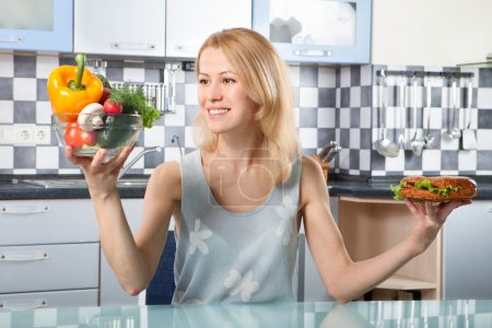 Photo for Woman choosing between vegetables and sandwich in the kitchen - Royalty Free Image
