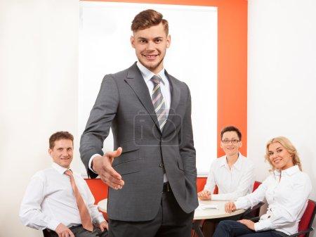 Photo pour Portrait d'homme d'affaires heureux offrant poignée de main et son équipe au bureau - image libre de droit