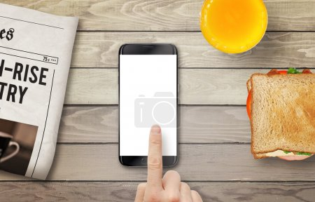 Smart phone with isolated display for mockup. Hand touching display. Newspaper, juice and sandwich on table. Top view.