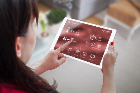 Photo pour Femme utiliser l'application pour smart domotiques sur tablette. Intérieur du salon en arrière-plan. - image libre de droit