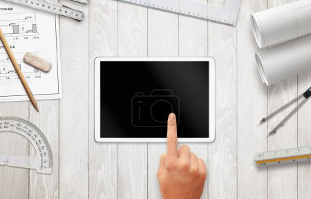 Tablet with blank screen for mockup on architect work desk. Construction projects, and drawing equipment.
