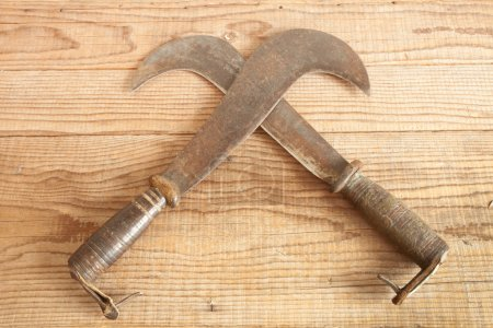 Two dated and used billhooks on wooden background
