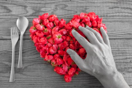 Heart made of red roses in wooden background, covered by an hand