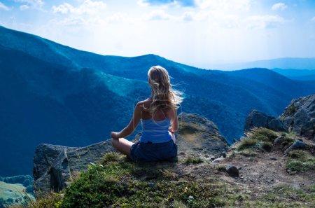 Photo pour Jeune femme blonde méditant dans le beau paysage de montagne. chaîne de montagnes des Carpates et ciel bleu . - image libre de droit