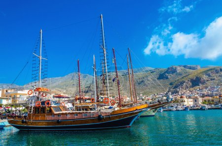 Big wooden yacht anchored in port Pothia, Greece