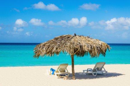 Tropical beach, sunbeds and palm tree umbrellas