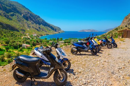 Scooters parked and sea bay with beach, Greece