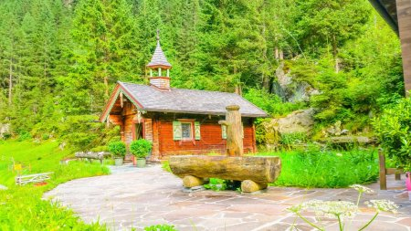 Wooden church and green pines, Austria, Alps