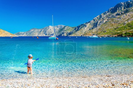 Sea bay on Greek Island with small boy at play