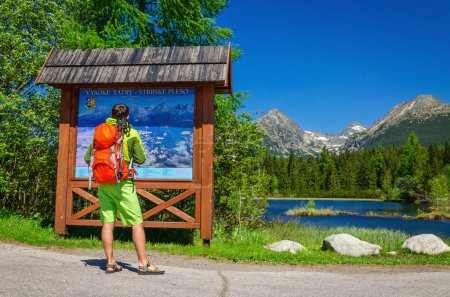 Man watching map of mountain trails
