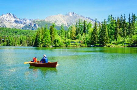 Father with child in paddle boat on mountain lake