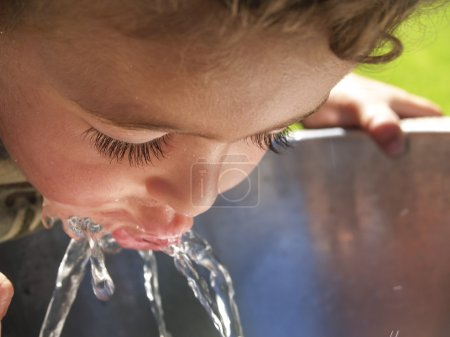 Little boy drinking cool fresh water from drinking fountain.