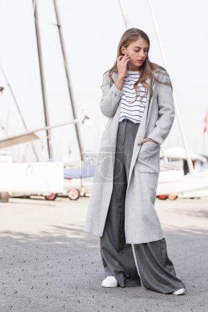 Photo pour Belle fille glamour chic, debout dans une tenue quotidienne moderne haute couture : pantalon gris, chemise blanche à rayures, gris longtemps sur les baskets de manteau et blanc taille. - image libre de droit