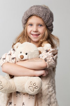 little girl taking small toy bear