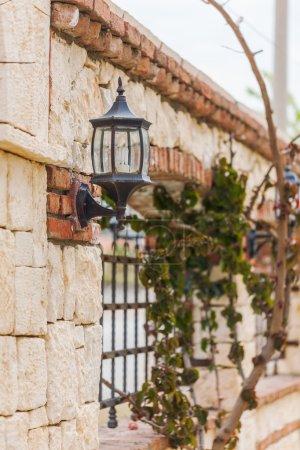 Photo pour Clôture de pierre avec grille en fer forgé et des lumières dans un style classique - image libre de droit