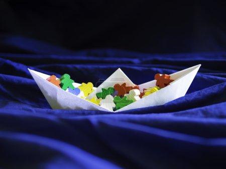 Immigration emigration migration concept, paperboat with meeples