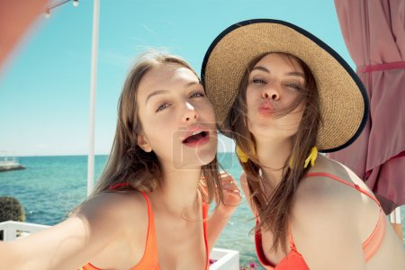 two smiling young women on beach making selfie