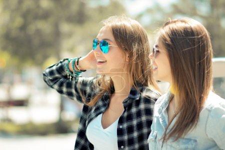 Beautiful ladies in sun glasses posing near vintage car cabriole