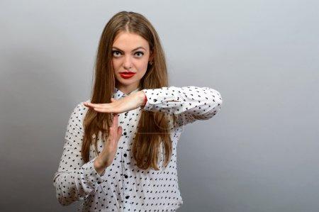 Photo pour Jeune femme montrant le temps geste de la main, frustré criant d'arrêter isolé sur fond de mur gris. Trop de choses à faire. Émotions humaines réaction d'expression faciale - image libre de droit