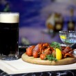 Black beer and crayfish with lemon and greens on a...