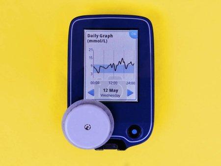 Photo pour CGM Dispositif de surveillance continue du glucose et capteur blanc. Graphique quotidien à l'écran. Fond jaune. Diabète de type 1. L'insuline dépend - image libre de droit