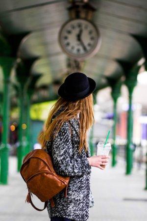 junges schönes Mädchen mit Hut und einem kurzen Kleid und einer Jacke auf einem Hintergrund aus grünen Stangen