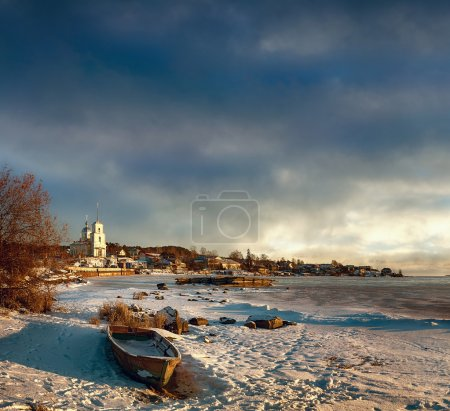 Russia. The Orthodox Church on the shore of a frozen lake. In the foreground an old boat. winter evening.