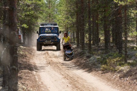 SUV on a forest road is catching a woman with a stroller. Off-road racing. Girvas 18.07.2015. Summer, Sand.