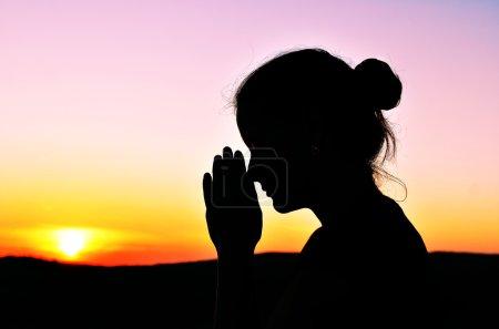 Photo pour Elle plia les mains en prière. magnifique coucher de soleil . - image libre de droit