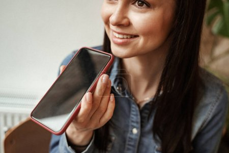 cheerful young woman recording voice message while holding smartphone