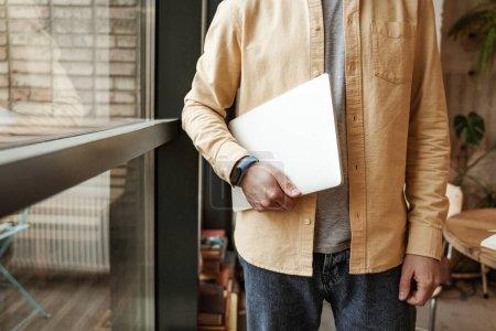 Ausgeschnittene Ansicht eines Freiberuflers mit Laptop am Fenster