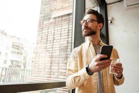 bärtiger Mann hält Smartphone in der Nähe von Fenster mit Glas Wasser