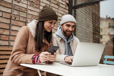 Photo pour Heureux pigistes chapeaux bonnet regardant ordinateur portable sur la table - image libre de droit