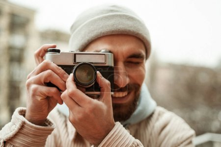 bearded photographer in beanie hat smiling while taking photo on retro camera