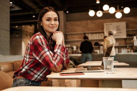 Photo pour Heureux pigiste assis sur le canapé dans le café - image libre de droit