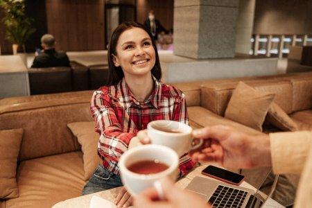 Photo pour Homme flou donnant tasse de thé à une femme heureuse - image libre de droit