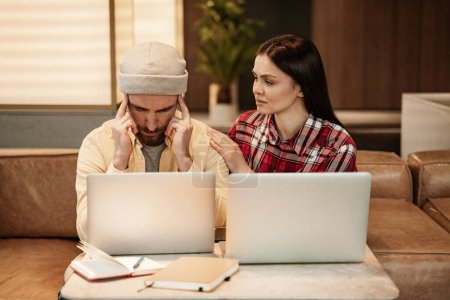 Photo for Woman calming stressed bearded freelancer near laptops - Royalty Free Image