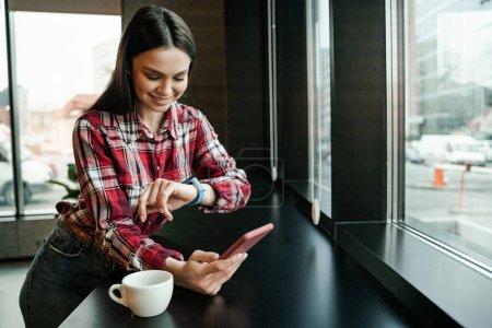 glückliche Frau schaut auf smarte Uhr, während sie Handy in der Nähe von Tasse auf Tisch hält